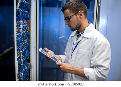 Side view portrait of young man wearing lab coat working with supercomputer and  checking data on digital tablet