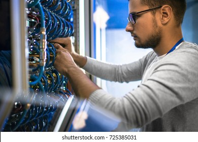 Side view portrait of young man wearing glasses connecting cables in server cabinet while working with supercomputer in data center - Shutterstock ID 725385031
