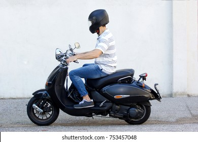 Side view portrait of young man in helmet riding a scooter on road