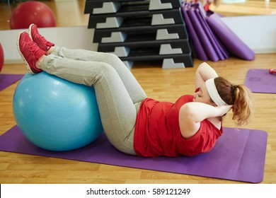 Side view portrait of young overweight woman working out in fitness studio: using big ball for sit ups with effort to lose weight
