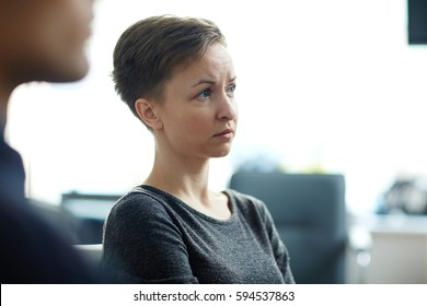 Side view portrait of young pale woman with short haircut, listening to seminar in group looking worried and sad