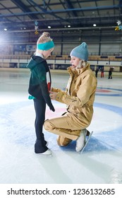 Side view portrait of young woman zipping up little girls jacket during figure skating training in indoor rink