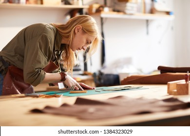 Side view portrait of young woman cutting leather patterns in atelier workshop, copy space