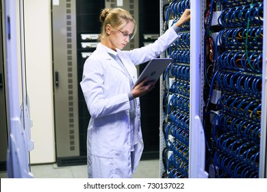Side view portrait of young woman wearing lab coat  working with supercomputer in research center, copy space