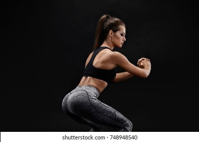 Side view portrait of a young woman doing squats on black background.