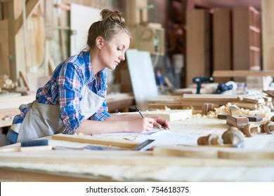Side view portrait of young woman making notes standing at table in modern workshop, copy space