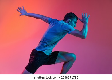 Side view. Portrat of Caucasian male athlete, runner training isolated on pink studio background with blue neon filter, light. Concept of action, motion, speed, healthy lifestyle. Copyspace for ad. - Shutterstock ID 2038891793