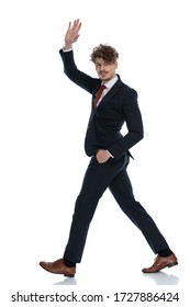 Side view of positive businessman waving with hand in pocket while wearing suit and walking on white studio background