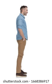 Side view of positive casual man smiling with both hands in pockets while wearing blue shirt, standing on white studio background