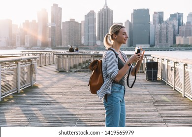 Side view of positive Caucasian woman wanderer with old fashioned instant camera in hands looking around for taking few pictures of American view, concept of weekend getaway to Brooklyn district