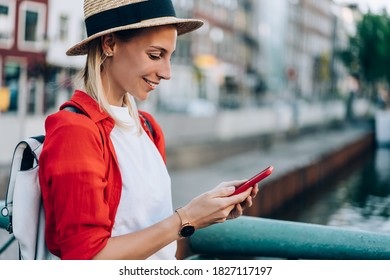 Side view of positive female in casual outfit with backpack and hat smiling while using modern wireless mobile phone during holiday in Europe