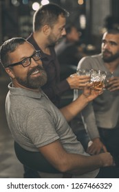 Side view of positive man wearing in spectacles and grey t shirt looking at camera and smiling. Bearded man holding glass of scotch. His friends standing behind and communicating.