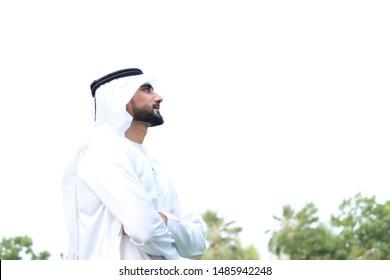Side view post of Saudi Emirati Arab man looking upwards wearing traditional kandura menswear with copy space