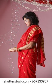 Side view of pregnant Indian lady holding oil lamp