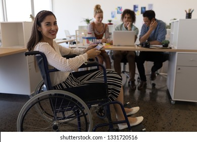 Side view of pretty disabled mixed-race female smiling at the camera in the office. Diverse business team is working in the background.