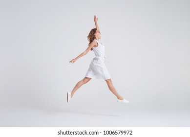 Side view of pretty girl in dress jumping isolated over background