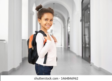 Side view of pretty little African school girl walking in school on break , smiling at camera. Cute and happy girl wearing in white blouse and jeans holding big bag pack. Concept of school.