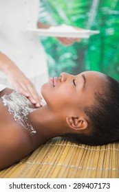 Side view of a pretty woman enjoying a salt scrub massage on the chest
