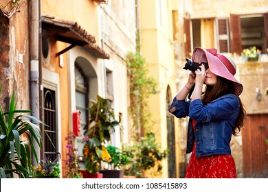 Side view of pretty woman in hat aiming with camera at Trastevere in Rome, Italy.