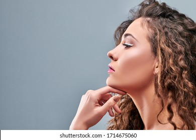 Side view of pretty woman touching chin on grey background. Copy space