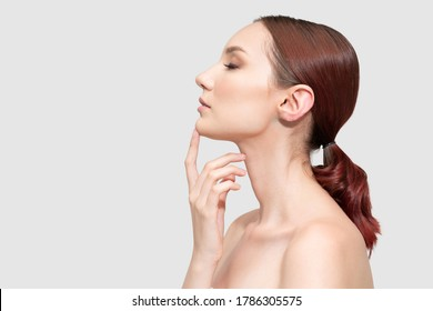 Side view of pretty young female model touching chin with finger
