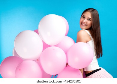 Side view of pretty young girl with air balloons posing at camera on blue background