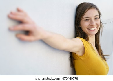Side view of pretty young woman with brown hair in yellow T-shirt standing at white wall with arms spread, looking at camera and smiling happily. Perspective