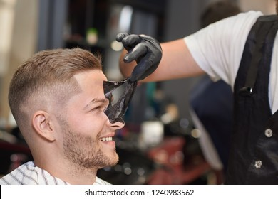 Side view of process of removing black mask from face of male client in barber shop. Barber in protective gloves taking away mask against dots while customer laughing. Concept of care.