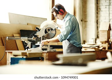 Side view of professional carpenter in protective earmuffs and eyewear sawing wood plank with electric circular saw in his workshop