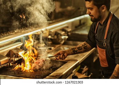 Side view of professional chef cooking delicious juicy beef steak on flaming grill. Handsome man with beard and tattoos on hand preparing food in modern restaurant kitchen.