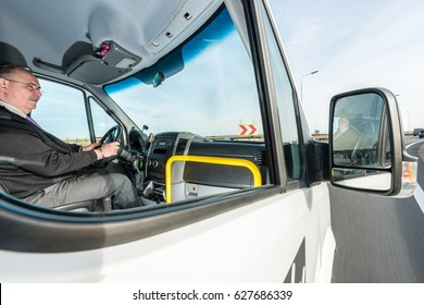 Side view of professional male cab driver riding taxi on highway