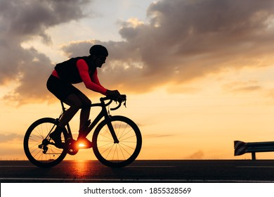 Side view of professional road cyclist on bright sport clothing and protective helmet riding outdoors with amazing sunset on background. Concept of active lifestyle.