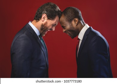 Side view profile of angry young colleagues are fighting each other with foreheads together, staring with hostile expressions. Isolated on red background