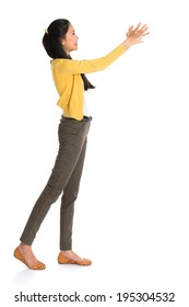 Side view or profile of an Asian girl arms up like holding something, full length standing isolated on white background.