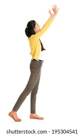 Side view or profile of an Asian girl arms up like pushing something away, full length standing isolated on white background.