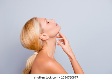 Side view, profile, half face portrait of pretty, charming, attractive woman enjoying, touching her perfect neck with fingers, having head back with closed eyes, moisturizing, hydration concept