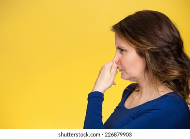 Side view profile portrait middle aged woman covers pinches her nose with hand looks with disgust, something stinks bad smell situation isolated yellow background. Human face expression body language