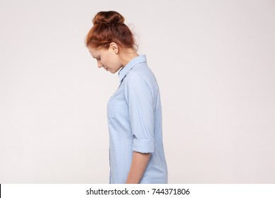 Side view, profile sad red head businesswoman. Isolated on gray background. Studio shot