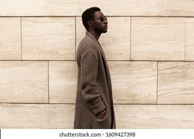 Side view profile stylish african man model wearing brown knitted cardigan, sunglasses on city street over brick wall background