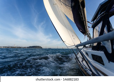 Side view of racing sailboat as it heads for the Bay Bridge in San Francisco Bay on a sunny day