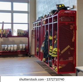 A side view of a rack of firefighters' gear and clothing in a firehouse. No personally identifiable names are shown. Concepts of emergency services, fire safety, and protection