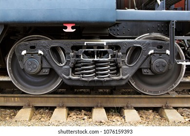 Side view of railroad car undercarriage showing wheels and springs