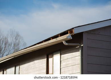 side view of rain gutter on apartment detaching from roof