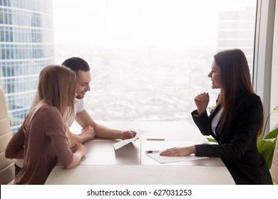 Side view of realtor and young couple sitting at office desk discussing property for sale. Potential buyers holding house plan, considering investment in home or taking loan to purchase real estate