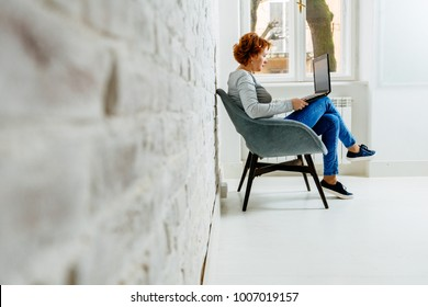 Side view of red hair woman with a tablet sitting on a chair near a brick wall over window in empty home or office