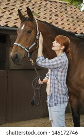 Side view of a red haired young woman with horse outside stable