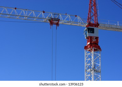 Side view of a red and white construction crane on a sunny day.