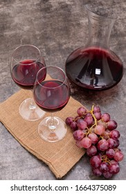 Side view red wine in jug and glasses on sackcloth on dark stone background vertical
