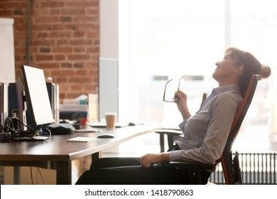 Side view relaxed business woman taking off eyeglasses resting leaning on comfortable chair sitting alone in modern office, take break, dreaming, feels good tranquil after work. Stress relief concept