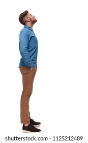 side view of relaxed casual man looking up at something while standing  on white background, full length picture